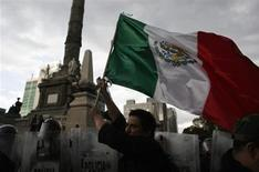 A demonstrator holds a Mexican national flag in front of riot policemen during a protest against the privatization of the state oil monopoly Pemex at the Angel of Independence in Mexico City July 1, 2013. REUTERS/Tomas Bravo