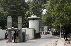 Полицейский и сотрудники службы безопасности охраняют въезд в консульство США в Лахоре 9 августа 2013 года. Вашингтон предостерег американских граждан от поездок в Пакистан и распорядился эвакуировать вспомогательный персонал консульства в Лахоре из-за угрозы атаки. REUTERS/Mohsin Raza