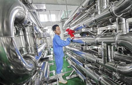 An employee wipes equipment on the production line of hawthorn red wine at a factory in Weifang, Shandong province July 28, 2013.REUTERS/China Daily/Files