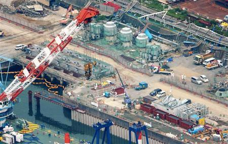 An aerial view shows workers wearing protective suits and masks work at a construction site (C) of the shore barrier to stop radioactive water from leaking into the sea, at the tsunami-crippled Fukushima Daiichi nuclear power plant in Fukushima, in this photo taken by Kyodo August 9, 2013. REUTERS/Kyodo