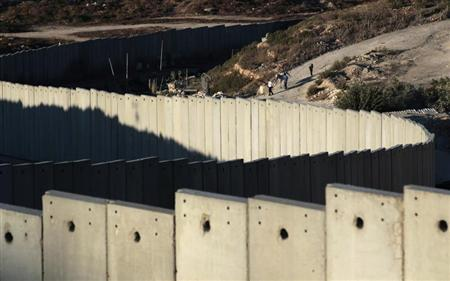 A section of the controversial Israeli barrier snakes around Shuafat refugee camp (R) in the West Bank near Jerusalem July 27, 2013. IREUTERS/Ammar Awad