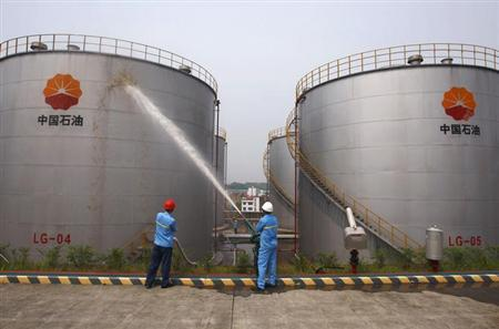 Employees spray water to cool down oil tanks at a storage facility, which belongs to one of China's biggest state-owned firms PetroChina oil, in Suijing, Sichuan Province, in this August 13, 2010 file photo. REUTERS/Stringer/Files