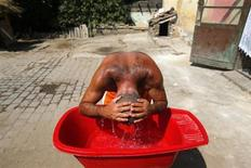 A Roma man cools himself at the impoverished outskirts of Ozd, northeastern Hungary, 155 km (96 miles) from Budapest August 7, 2013. REUTERS/Laszlo Balogh