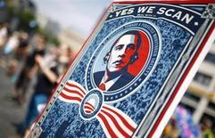 Manifestante ergue um cartaz com imagem do presidente dos EUA, Barack Obama, durante protesto em apoio ao ex-prestador de serviço de uma agência de espionagem dos EUA Edward Snowden, em Frankfurt. Obama reuniu-se discretamente na quinta-feira com os executivos-chefes da Apple, da AT&T e de outras empresas de tecnologia, além de ativistas em defesa da privacidade, para discutir as práticas de vigilância do governo, segundo relato publicado pelo site Politico. 27/07/2013. REUTERS/ Kai Pfaffenbach