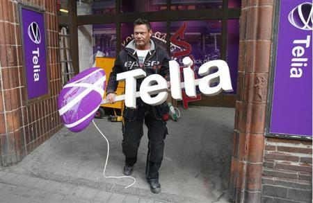 A workman prepares to install a sign with TeliaSonera's new corporate logo, outside a store in downtown Stockholm May 12, 2011. REUTERS/Bob Strong