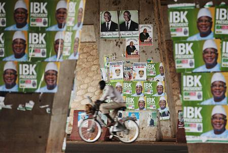 A man rides a bicycle past electoral campaign posters in Bamako August 9, 2013. REUTERS/Joe Penney