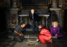 Silvano Vinceti (top), head of Italy's National Committee for the Promotion of Historic and Cultural Heritage, looks on as researchers open the tomb in the stone church floor above the family crypt of Florentine silk merchant Francesco del Giocondo at the Santissima Annunziata basilica in Florence August 9, 2013. REUTERS/Stefano Rellandini