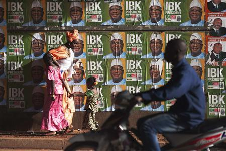 People walk past electoral campaign posters in Bamako, Mali, August 9, 2013. REUTERS-Joe Penney