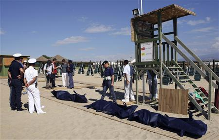Italian police stand guard next to bodies of migrants who drowned after a shipwreck, at La Playa beach in Catania on Sicily island August 10, 2013. REUTERS-Antonio Parrinello