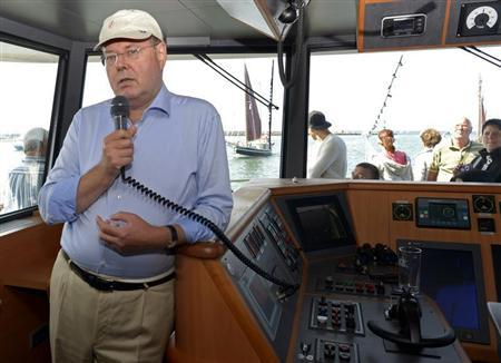 Peer Steinbrueck, the Social Democratic party (SPD) candidate in the upcoming general elections, talks to tourists with a microphone from the bridge of a boat, during a harbour trip in Warnemuende, August 9, 2013. REUTERS/Fabian Bimmer