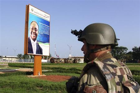 A French soldier stands in front of a poster of ousted President Francois Bozize outside M'poko international airport in Bangui March 28, 2013. REUTERS/Alain Amontchi