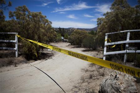 The remains of a home owned by 40-year-old James Lee DiMaggio, a suspect in the murder of 2 people, is shown beyond Sheriffs' tape in the Boulevard neighborhood of San Diego County August 7, 2013. DiMaggio is suspected in the slaying of Christina Anderson, 44, and is believed to have kidnapped one or both of Anderson's children, 16-year-old Hannah and 8-year-old Ethan. REUTERS/Sam Hodgson