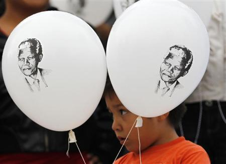 A child holds up balloons with images of former South African President Nelson Mandela as he participates in a celebration to mark Mandela's 95th birthday at the Angel de la Independencia monument in Mexico City July 18, 2013. REUTERS/Henry Romero