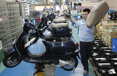 Men work on the assembly line at a Piaggio scooter and motorcycle factory in Vietnam's northern Vinh Phuc province, outside Hanoi July 11, 2013. REUTERS/Kham