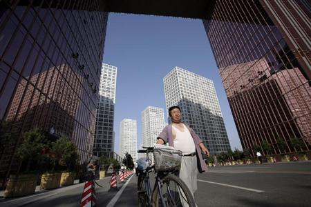 A news vendor walks with a bicycle at the Central Business District in Beijing July 9, 2009. REUTERS/Jason Lee
