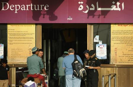 A police officer checks documents of a traveller outside the departure lounge Sanaa International Airport August 7, 2013. REUTERS/Khaled Abdullah