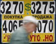 Мужчина проходит мимо пункта обмена валют в Москве 31 мая 2012 года. Рубль стабилен утром понедельника и сохраняет предпосылки для роста в преддверии налогового периода, стартующего 15 августа, на фоне высоких нефтяных цен и в связи с близким расположением области повышенных налоговых интервенций ЦБ. REUTERS/Maxim Shemetov