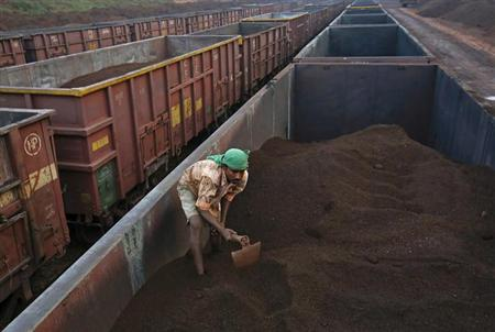 A worker levels the iron ore in a freight train at a railway station at Chitradurga in Karnataka November 9, 2012. REUTERS/Danish Siddiqui /Files