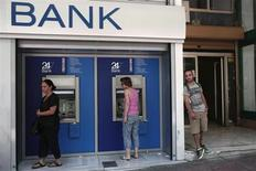 Pessoas realizam transações bancárias em caixas eletrônicos em Atenas, na Grécia. A Grécia atingiu facilmente suas metas fiscais nos primeiros sete meses do ano, sustentada por uma ajuda de recursos dos bancos centrais da zona do euro e da União Europeia, mostraram dados do Ministério das Finanças nesta segunda-feira. 12/08/2013 REUTERS/Yorgos Karahalis