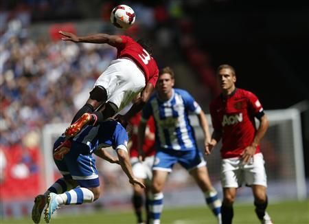 Manchester United's Patrice Evra flies over Wigan Athletic's Shaun Maloney during their English Community Shield soccer match at Wembley Stadium in London, August 11, 2013. REUTERS/Eddie Keogh