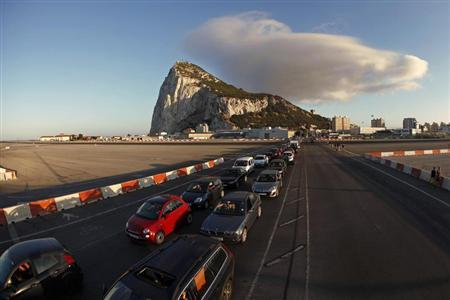 Drivers wait in line along the road of the Gibraltar International airport to enter to Spain at its border with the British territory of Gibraltar in front of the Rock (rear) in Gibraltar, south of Spain August 9, 2013. REUTERS/Jon Nazca