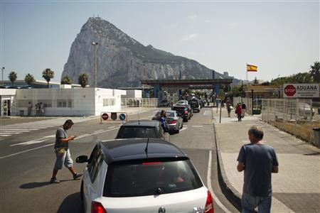 Drivers wait in line to enter the British territory of Gibraltar at its border with Spain in front of the Rock of Gibraltar (rear), a monolithic limestone promontory, in La Linea de la Concepcion, southern Spain August 12, 2013. Britain warned Spain on Monday it might take legal action to try to force Madrid to abandon tighter controls at the border with the contested British overseas territory of Gibraltar in what it called an