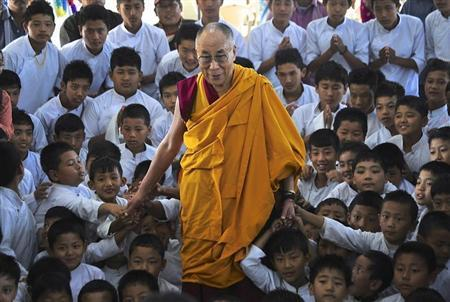 Exiled Tibetan spiritual leader the Dalai Lama poses for a picture with the students of a Tibetan school after inaugurating its auditorium at Gurupura in the southern Indian state of Karnataka July 14, 2013 file photo. REUTERS/Stringer