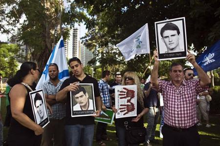 Israeli protesters hold pictures of their relatives who were killed by Palestinians, during a protest against the government's plan to free Palestinian prisoners, in Tel Aviv August 12, 2013. REUTERS/Nir Elias