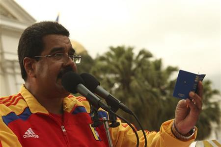 Venezuela's President Nicolas Maduro (C) holds a copy of the Venezuelan constitution as he speaks during a rally in Caracas in this handout photo provided by Miraflores Palace on August 3, 2013. REUTERS/Miraflores Palace/Handout via Reuters