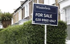 An estate agent's sign is posted outside a terraced house in north London August 2, 2013. REUTERS/Suzanne Plunkett