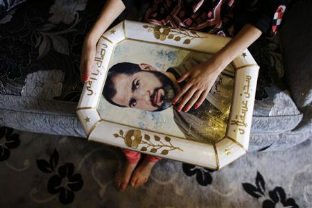 Verde holds a framed portrait of her relative, Palestinian prisoner Jamil Nabi Annatsheh, ahead of his release from an Israeli prison, in the West Bank city of Hebron August 13, 2013. REUTERS/Ammar Awad
