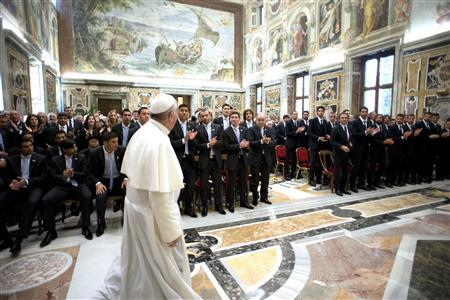 Pope Francis walks in front of members of the soccer teams of Argentina and Italy as he arrives for a private audience at the Vatican, August 13, 2013. REUTERS/Osservatore Romano