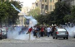 Un partidario del derrocado presidente egipcio Mohamed Mursi patea un contenedor de gas lacrimógeno contra la policía durante enfrentamientos en El Cairo. Agosto 13, 2013. REUTERS/Asmaa Waguih. Seguidores y detractores de Mursi se enfrentaron el martes en las céntricas calles de El Cairo, lanzándose piedras mutuamente mientras la policía utilizaba gases lacrimógenos.