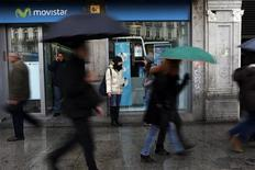 A man talks on his cell phone outside a Movistar store as people walk past in Madrid February 28, 2013. REUTERS/Susana Vera
