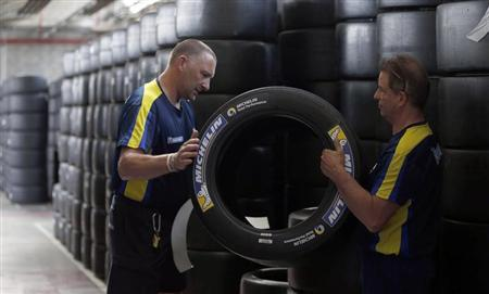 Workers hold a motorsport racing tyre stocked in the Michelin tyre company's factory in Clermont-Ferrand, central France, July 10, 2013. REUTERS/Regis Duvignau