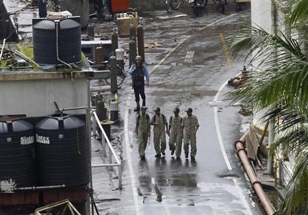 Indian Navy personnel walk past a guard at the naval dockyard in Mumbai August 14, 2013. REUTERS/Danish Siddiqui