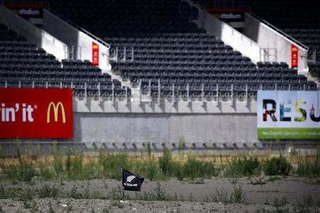 A small flag can be seen in the middle of the severely damaged rugby stadium in the New Zealand city of Christchurch March 11, 2013. REUTERS/David Gray