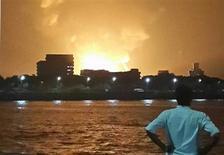 """Мужчина смотрит на горящую подлодку """"Синдуракшак"""" в Мумбаи 13 августа 2013 года. Несколько членов экипажа индийской дизельной подлодки погибли после взрыва и пожара в среду, когда корабль находился в доке в Мумбаи, сказал министр обороны Индии А.К.Энтони, не вдаваясь в подробности. REUTERS/Vikalp Shah"""