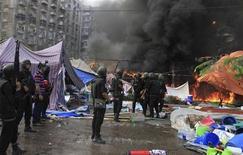"""Спецназовцы зачищают лагерь сторонников """"Братьев-мусульман"""" и свергнутого президента Мохаммеда Мурси в Каире 14 августа 2013 года. По крайней мере 30 человек были убиты египетской полицией в ходе операции по зачистке лагеря сторонников свергнутого президента Мохаммеда Мурси в Каире, сообщила организация """"Братья-мусульмане"""". REUTERS/Stringer"""