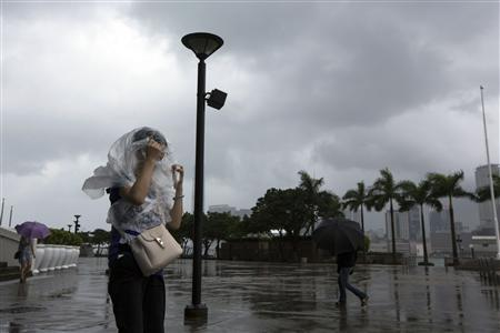 A woman braves the wind at the Golden Bauhinia Square as Typhoon Utor approaches Hong Kong August 14, 2013. REUTERS/Tyrone Siu