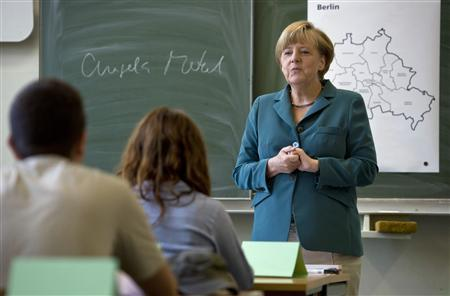 German Chancellor Angela Merkel conducts a lecture, after writing her name on a board, at a classroom in Heinrich Schliemann Gymnasium, a secondary school in Berlin, August 13, 2013. REUTERS/Odd Andersen/Pool