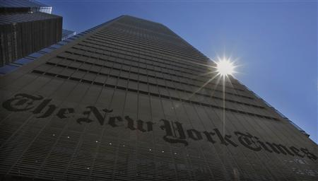 The sun peaks over the New York Times Building in New York August 14, 2013. REUTERS/Brendan McDermid