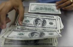 Una mujer cuenta dólares estadounidenses en una casa de cambios en Rangun. El euro cotizó con pocos cambios frente al dólar, pese a datos que mostraron que la zona euro emergió en el segundo trimestre de su más prologada recesión. REUTERS/Soe Zeya Tun (MYANMAR - NEGOCIOS)