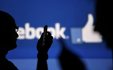 Men are silhouetted against a video screen with an Facebook logo as he poses with an Nokia Lumia 820 and Samsung Galaxy S4 in this photo illustration taken in the central Bosnian town of Zenica, August 14, 2013. REUTERS/Dado Ruvic