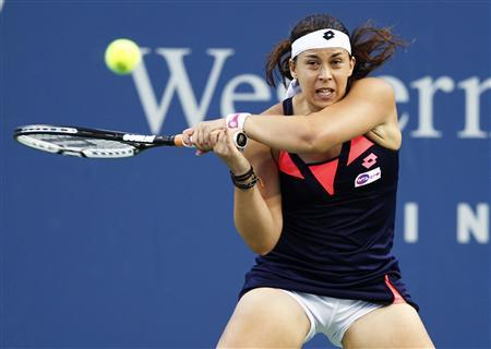 Marion Bartoli of France hits a return to Simona Halep of Romania during their women's singles match at the Cincinnati Open tennis tournament in Cincinnati, Ohio August 14, 2013. REUTERS/John Sommers II