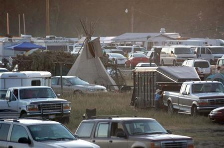 A traditional tipi is surrounded by cars as the parking lot fills up for the Oglala Nation Pow Wow and Rodeo in Pine Ridge, South Dakota, August 4, 2006. REUTERS/Jonathan Ernst