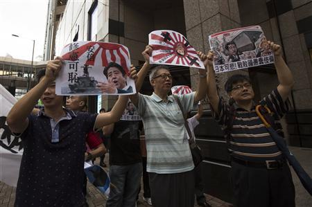 Anti-Japan protesters carry posters depicting Japanese Prime Minister Shinzo Abe as they march to the Japanese consulate in Hong Kong August 15, 2013. REUTERS/Tyrone Siu