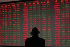 Мужчина смотрит на экран с рыночной информацией в брокерской конторе в Шанхае 6 апреля 2011 года. Азиатские фондовые рынки снизились в четверг из-за неуверенности инвесторов в сроках сокращения стимулов ФРС и локальных факторов. REUTERS/Aly Song