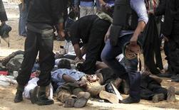 """Сторонники """"Братьев-мусульман"""" и Мохаммеда Мурси лежат лицом к земле после разгона протестующих в Каире 14 августа 2013 года. Египетская армия наделила себя чрезвычайными полномочиями на месяц и ввела комендантский час в столице и провинциях после разгона сторонников свергнутого президента-исламиста Мохаммеда Мурси. Мир осудил насилие и убийство сотен человек в самый кровавый день современной истории Египта. REUTERS/Mohamed Abd El Ghany"""