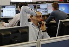 Дилер компании IG Index, предоставляющей услуги беттинга, разговаривает с клиентом в Лондоне 7 августа 2013 года. Европейские фондовые рынки снижаются под давлением швейцарской страховой компании Zurich Insurance, показавшей слабые результаты второго квартала. REUTERS/Luke MacGregor